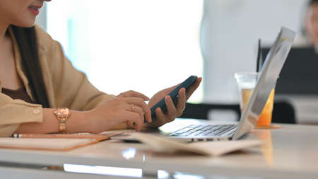Side view of businesswoman hands using smartphone while working with laptop and stationery