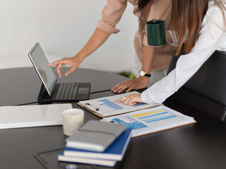 Cropped shot of two businesspeople working with digital tablet and business paperwork in meeting room Imagens