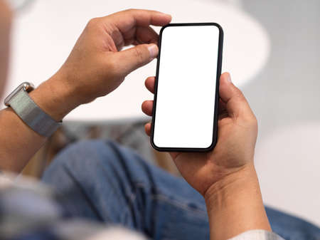 Close up view of man freelancer hands using smartphone with mock up screen in blurred background, clipping path Stock Photo
