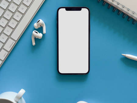 Top view of creative flat lay workspace with smartphone, earphone and supplies on light blue background, clipping path