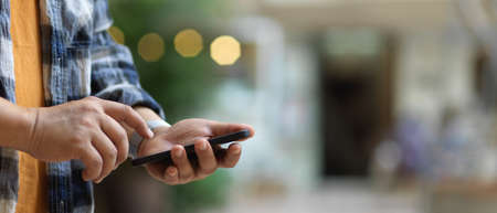 Close up view of a man touching on smartphone screen while standing in blurred background
