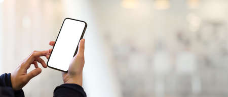 Close up view of female hand touching smartphone in blurred background with copy space, clipping path