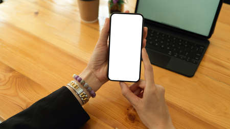 Top view of businesswoman hands holding smartphone and showing mock up screen to camera, clipping path Standard-Bild