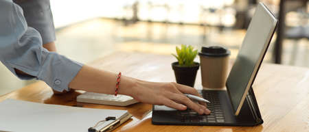Side view of female office worker hand typing on tablet keyboard on office table with paperwork