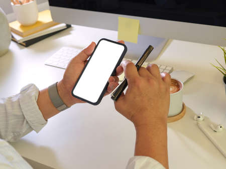 Close up view of male using smartphone with mock up screen and holding pen in his hand at workplace, clipping path