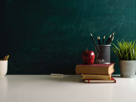 Close up view of books and school elements on study table in class room with chalkboard wall background