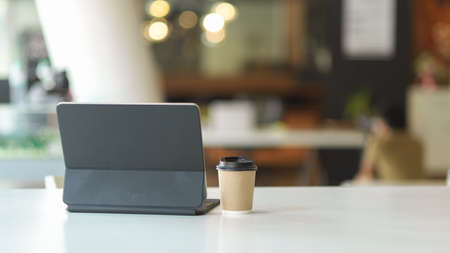 Close up view of portable workspace with digital tablet, paper cup and copy space in cafeteria Standard-Bild