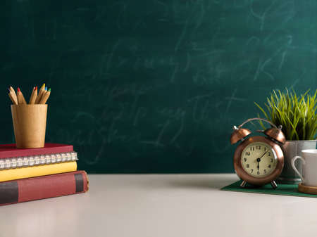 Close up view of study table with school elements, cup, clock and copy space in class room with chalkboard background Standard-Bild