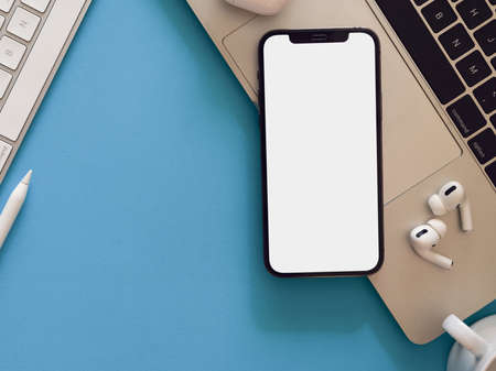 Creative flat lay workspace with smartphone, laptop, earphone and copy space on light blue background, clipping path