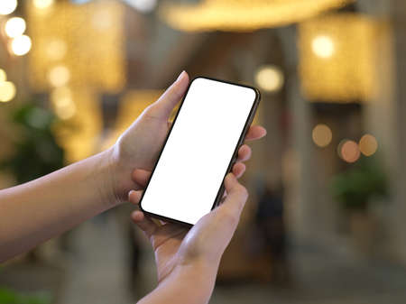Cropped shot of female hands holding smartphone with mock up screen in bokeh background, clipping path
