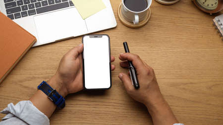 Overhead shot of businessman holding smartphone and pen in his hand on wooden workspace, clipping path
