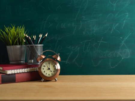 Education concept, study table with clock, stationery, plant pot and copy space on wooden table with chalkboard wall background