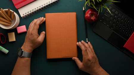 Overhead shot of male hands holding book on dark green study table with stationery and tablet keyboard