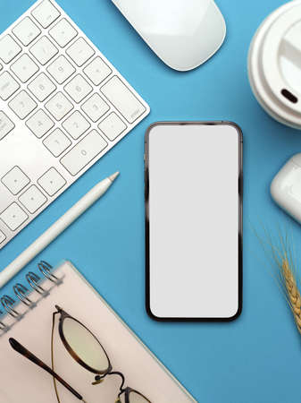 Creative flat lay workspace with smartphone, computer devices, stationery and eyeglasses on light blue background, clipping path