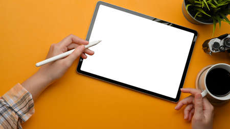 Top view of female freelancer hands using digital tablet with stylus pen on stylish workspace, clipping path