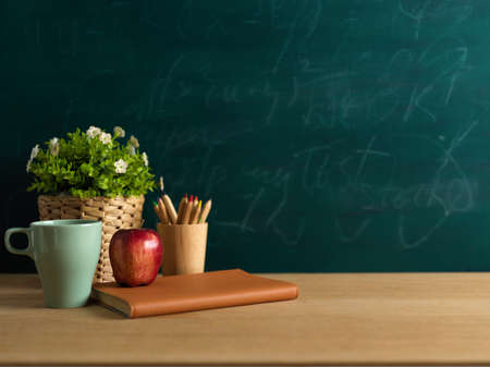 Close up view of study table with notebook, apple, pencils and plant pot in classroom with blackboard background Standard-Bild