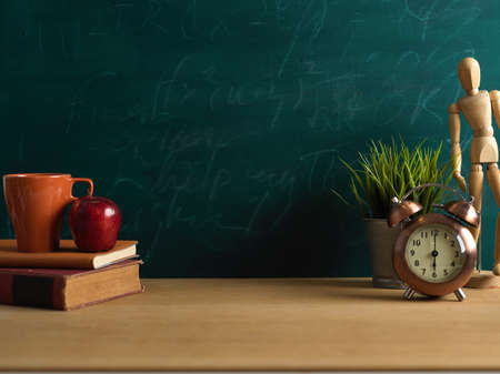 Study table with books, cup, apple, decorations and copy space in blackboard background, school element
