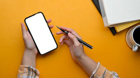 Top view of female freelancer working with smartphone and holding pen in her hand on stylish workspace, clipping part Standard-Bild