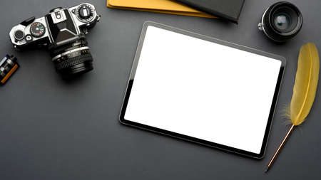 Top view of creative flat lay workspace with digital tablet, camera and supplies, clipping path
