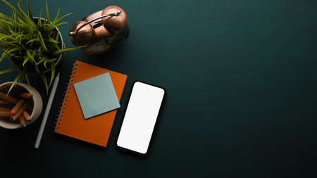 Top view of workspace with smartphone, stationery, decorations and copy space on dark green table, clipping path