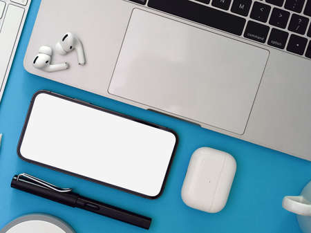 Creative flat lay workspace with smartphone, laptop, earphone and supplies on light blue background, clipping path, top view