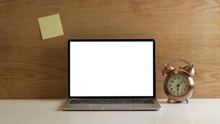Close up view of workspace with mock up laptop, clock and sticky note on wooden wall, clipping path