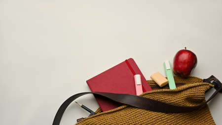 Mock up scene, top view of school bag with book, stationery and apple on white background