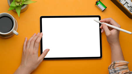 Top view of female hands using digital tablet with stylus pen on yellow  table, clipping path