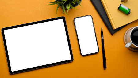 Stylish flat lay workspace with tablet, smartphone, stationery, film, coffee cup and plant pot on yellow table, clipping path Standard-Bild