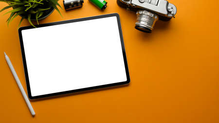 Top view of stylish workspace with digital tablet, camera, film and plant pot on the table, clipping path