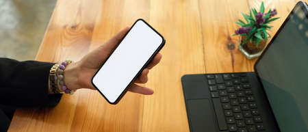 Side view of businesswoman in black suit holding mock up smartphone in her hand on office desk, clipping path