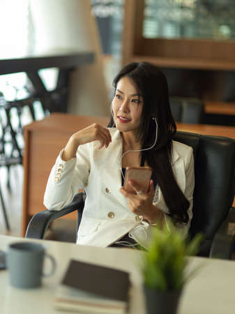 Portrait of businesswoman takes short time-out in office work using earphone and smartphone to relax