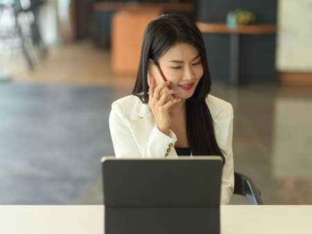 Portrait of young businesswoman smiling and talking on the phone while sitting at workplace