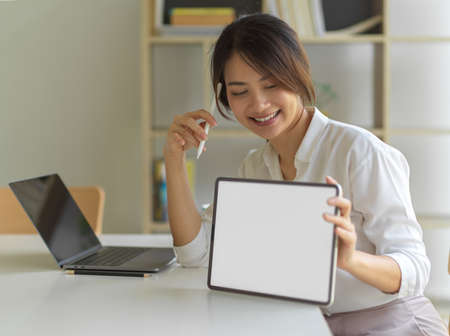 Portrait of female smiling and showing digital tablet with mock up screen on workspace in home office room, clipping path