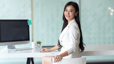 Portrait of businesswoman looking back and smiling to camera while sitting in modern office room
