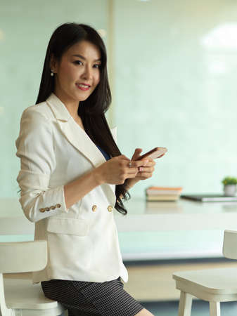 Portrait of businesswoman smiling to camera and using smartphone while standing in office room Reklamní fotografie