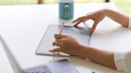 Side view of female hand with stylus pen working with digital tablet on white table in home office room
