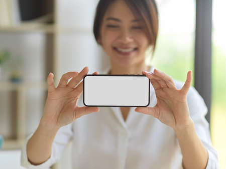 Portrait of smiling female hands holding smartphone and showing mock up smartphone to camera, clipping path
