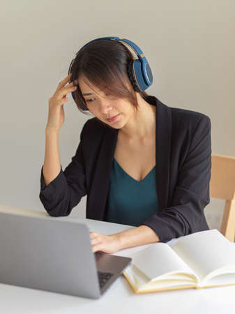 Portrait of businesswoman concentrating on her work while using headphone, laptop and book in office room