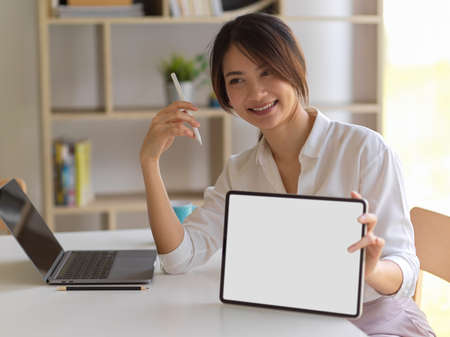 Portrait of female smiling and showing digital tablet with mock up screen in home office room, clipping path