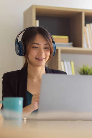 Portrait of happy businesswoman smiling and using headphone while working with laptop in home office room
