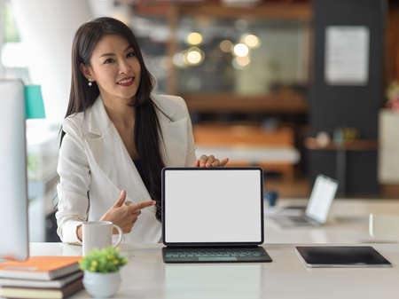 Close up view of businesswoman in white suit presenting digital tablet and pointing to mock up screen in office room, clipping path