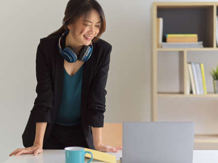 Portrait of happy businesswoman smiling while standing in comfortable office room