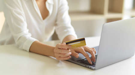 Cropped shot of female hand with credit card and typing on laptop keyboard while online shopping at home