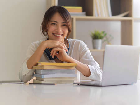 Portrait of female university student smiling to camera while sitting at study table with laptop and stack of books Reklamní fotografie