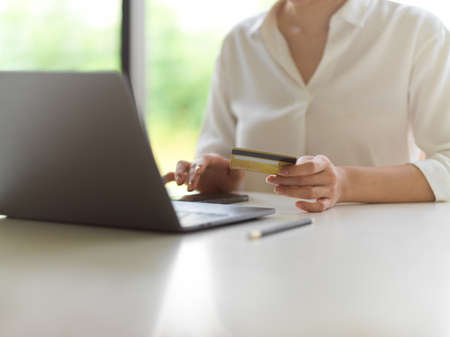 Cropped shot of female hand holding credit card and touching smartphone screen on white desk with computer laptop