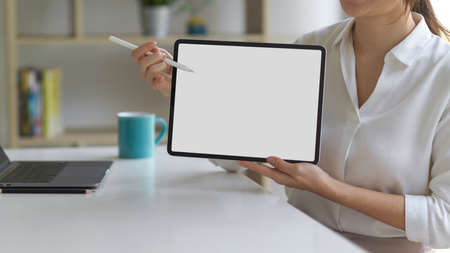 Female in white shirt presenting digital tablet with mock up screen and using stylus pointing on the screen