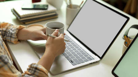 Side view of female hands holding coffee cup while working with laptop on office desk, clipping path