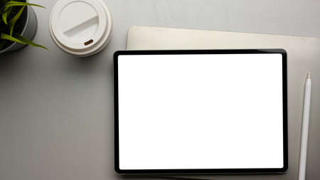 Digital tablet with mock up screen on office desk with paper cup and laptop, clipping path, top view