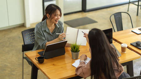 Top view of two female office workers consulting their work with stationery in comfortable meeting room Stock Photo